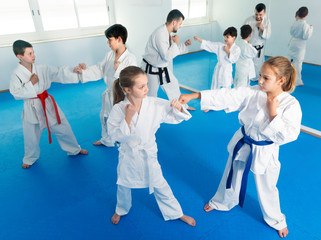 Happy kids sparring in pairs in karate class