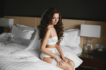 Beautiful sexy and fashionable brunette model girl, in white lingerie and stockings, sits and posing on the bed in bedroom - wedding preparation of young stylish bride