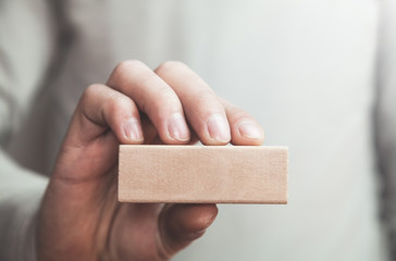 Man showing blank wooden block.
