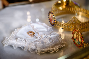 White pillow in form of heart and golden wedding rings on it