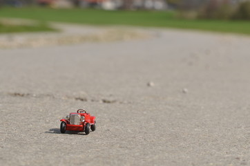 Small red oldtimer toy car on a concrete road outdoors