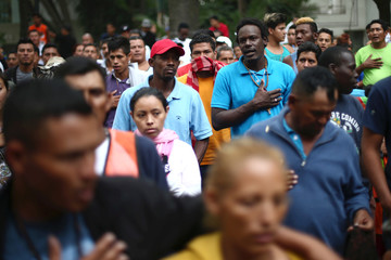 Central American migrants, moving in a caravan through Mexico, sing the national anthem during a demonstration outside the Embassy of Honduras in Mexico City