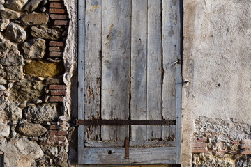 Old stone wall with wooden shutters
