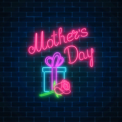 Glowing neon banner of mothers holiday on dark brick wall background. Spring world mothers day greeting card