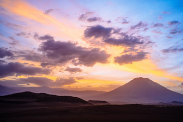 Scenic view of landscape and mountain against cloudy sky at sunset