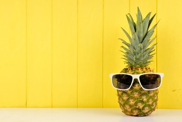 Hipster pineapple with trendy sunglasses against yellow wood background. Minimal summer concept.