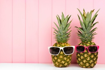 Hipster pineapples with trendy sunglasses against pink wood background. Minimal summer concept.