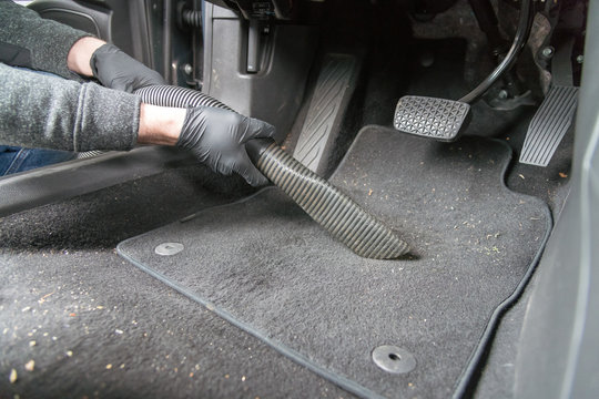 man cleaning car carpet with vacuum cleaner