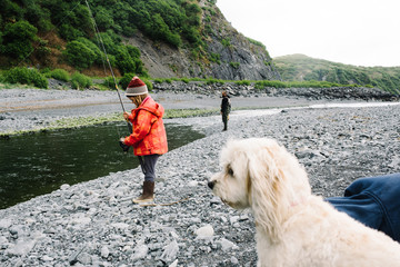 Young girl fishing with her father and dog