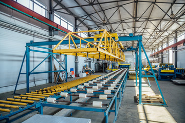 Insulation sandwich panel production line. Machine tools, roller conveyor in workshop