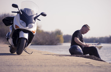 The motorcyclist takes a break near the lake to read the driving map
