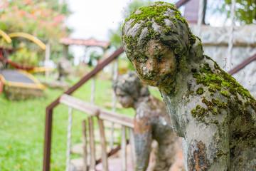 escultura abandonada en jardin con mirada triste