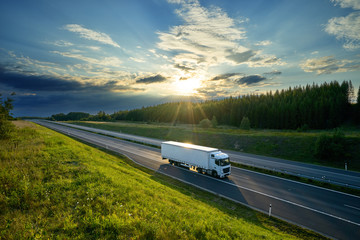 Fotobehang - White truck driving on the highway in the countryside in the rays of the sunset with dramatic clouds