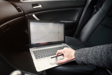 business man working while being in the car. man looks at the Stock market or forex trading graph and candlestick chart suitable for financial and makes a plan.