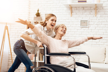 Girl is nursing elderly woman at home. Girl is riding woman in wheelchair. Woman feels like flying.