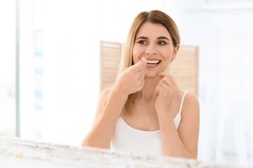 Young woman flossing her teeth in bathroom
