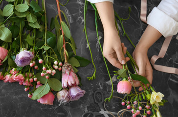 Female florist creating beautiful bouquet at table, top view