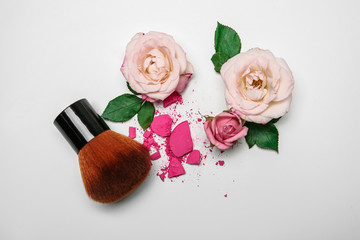 Flat lay composition with makeup brush and flowers on white background