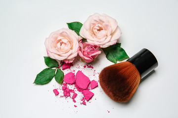 Composition with makeup brush and flowers on white background