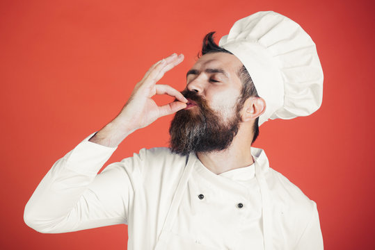 Professional chef man showing sign for delicious. Male chef in white uniform with perfect sign. Serious satisfied bearded chef, cook or baker gesturing excellent. Cook with taste approval gesture.
