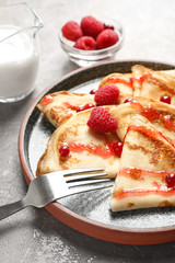 Thin pancakes served with syrup and berries on plate