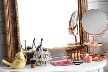 Table with beautiful mirror, cosmetics and tools in modern makeup room