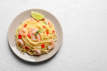 Plate with spaghetti and shrimps on light background, top view