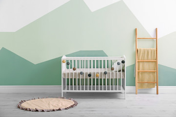 Baby room interior with crib near wall
