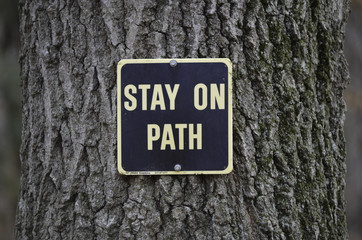 Stay on path sign posted to oak tree
