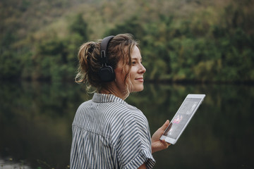 Woman alone in nature listening to music with headphones and digital tablet music and relaxation concept