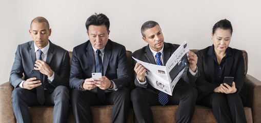 Business people busy with mobile and reading newspaper
