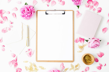 Workspace with clipboard, pastel roses and accessories on white background. Flat lay, top view. Blogger of freelancer concept