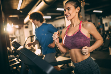 Fototapeten Fitness Horizontal photo of attractive woman jogging on treadmill at health club.