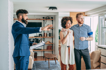 Young couple consulting with financial adviser at home.