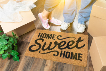 Man and Woman Standing Near Home Sweet Home Welcome Mat, Moving Boxes and Plant Wall mural
