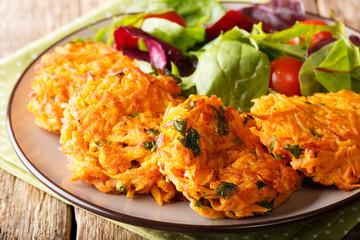 Vegetarian food: hot pancakes made from sweet potatoes and fresh mix salad close-up. horizontal