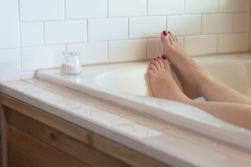 Women's feet with dark purple nail polish in a luxurious bathtub surrounded by white subway tile, with wood along the side. a small glass container of pink bath salts rests at the edge.