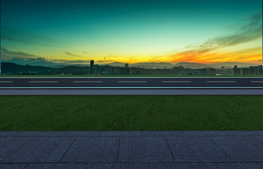 Side angle view empty asphalt road with grass ,stone marble floor and sunrise background . Mixed media .