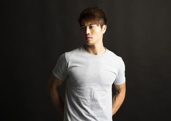 Portrait of young man standing in front of black background.
