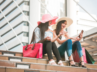 Two beautiful young women sitting on the stairs and using smart phone after enjoying in shopping