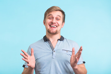 Portrait of happy university student guy pulling hands, laughing.