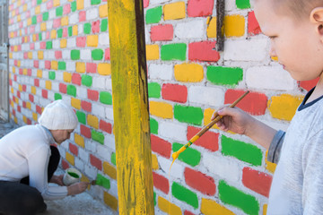 Happy caucasian child paints a brick wall with paint brush in different colors. Red, blue, yellow, green. Capacity with paint and hands close-up view