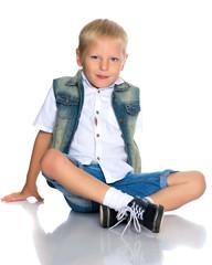 little boy is sitting on the floor