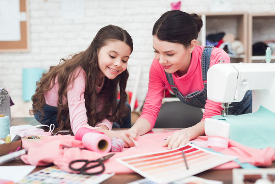 Mom and little daughter together sew clothes.