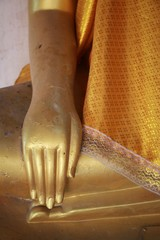 Flower on the hand of Buddha image god within gold colored in the Ayutthaya historical park - Thailand