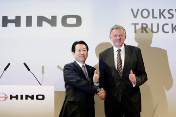 Hino Motors President Yoshio Shimo and Volkswagen Truck & Bus GmbH CEO Andreas Renschler shake hands as they pose for pictures during their joint news conference in Tokyo