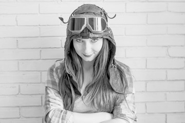 Portrait of a girl in pilot's cap and glasses on a brick wall background, black and white photo