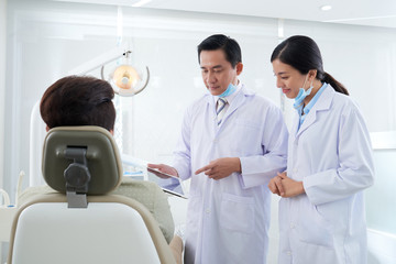 Dentists discussing information on tablet computer