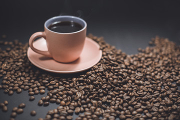 Cup of black coffee and roasted coffee beans.