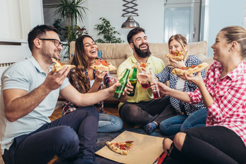 Group of young friends eating pizza.Home party.Fast food concept.